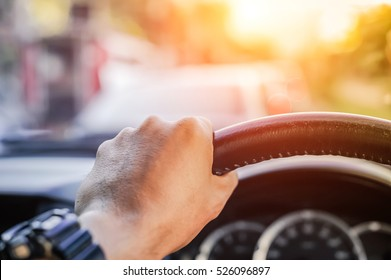 Driver's hand on the steering wheel inside of a car on road, a man driving a car in city Rush hour Traffic congestion Discomfort Drive at low-speed morning sun view