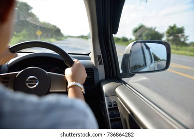 Driver's hand on steering wheel inside of a car, driving and looking wing mirror, women driving