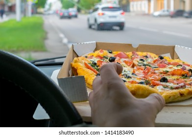 the driver's hand takes a piece of pizza, the packaging of which lies on the windshield panel of the parked car on the background of the city roadway