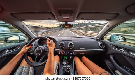 Driver's hands on a steering wheel of a car and woman in the passenger seat. Road trip on the Italians road.