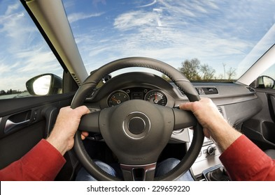 Driver's hands on steering wheel of car