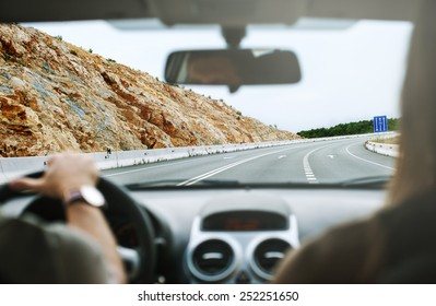 driver's hands on steering wheel inside of a car,travel in car,selective focus on the highway