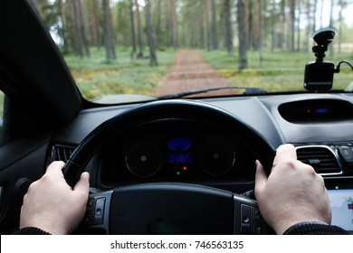 Driver's hands on the steering wheel taking photo scenic road among green forest perspective from his smartphone inside of a car with, road trip travel concepts