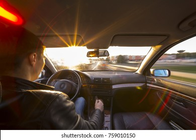 Driver's hands on steering wheel inside of a car and sunset sun with lens flare
