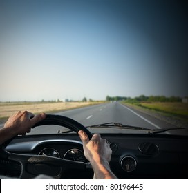 Driver's hands on a steering wheel of a retro car during riding on an empty asphalt road
