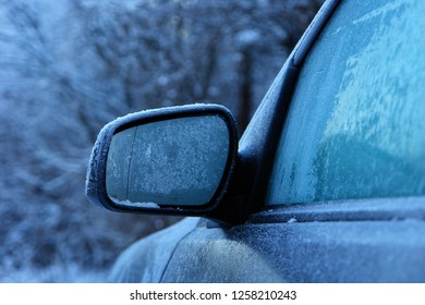 Driver's mirror and side window of the car in frost