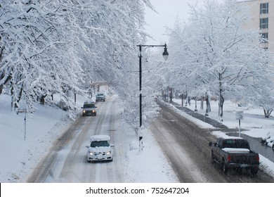 Drivers navigate a snow covered road while snowing