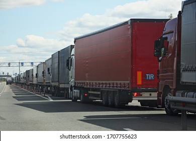 Drivers strike, big queue of trucks with semi-trailers to the sanitary and weight control point in Sunny summer day, rear side view in perspective