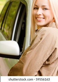 Driver-woman of car stands about cowl and smiles against summer nature.
