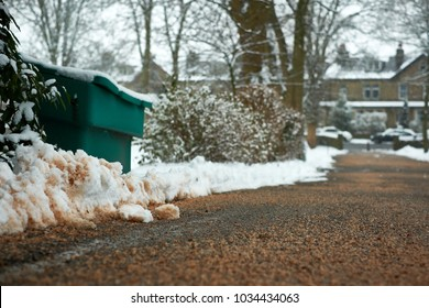 A driveway is covered in salt and grit from a salt bucket to keep access open during snowy weather.