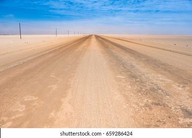 Driving across the Namib Desert in Western Namibia. Endless straight sand, gravel and salt roads