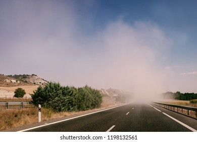 Driving along an ashpelt road with a white line on road trip into a dust cloud created by work taking place in the fields along the roadside