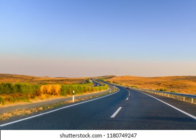 Driving along empty winding roads in Andalucia, Spain near Extremadura at the end of the summer with a golden sunrise lighting the dry fields and a blue sky. A road trip adventure
