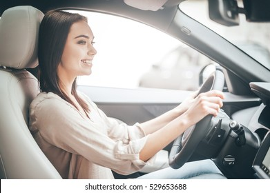 Driving around city. Young attractive woman smiling and looking straight while driving a car