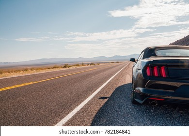 Driving in a black Ford Mustang GT through the Death valley in Nevada. Amazing road trip adventure. August 10, 2017, USA.