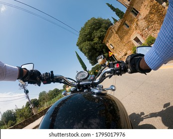 Driving a black old motorbike with wide handlebar on an asphalt road under a blue sunny sky