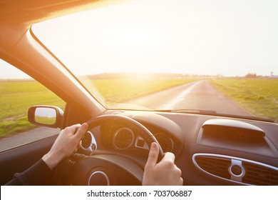 driving car, hands of driver on steering wheel, travel background