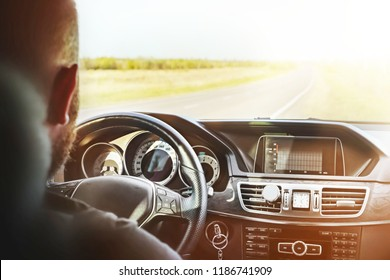 driving a car, a man with a beard sitting behind the wheel of a car and holding the wheel