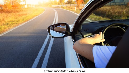 Driving a car on empty road on sunny day