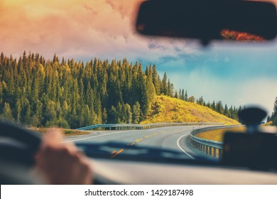 Driving a car on mountain road. View from windscreen of beautiful nature of Norway.