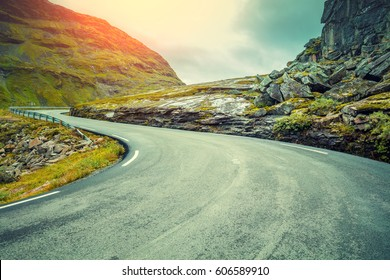 Driving a car on mountain road. Road among mountains with dramatic stormy cloudy sky. Landscape. Beautiful nature Norway.