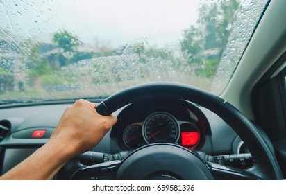 Driving car on the road, Driver's hands on the steering wheel inside of a car on a rainy day
