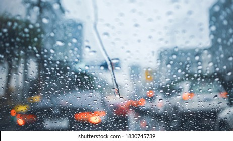 driving car on road in the rain with raindrop over the wind shield, traffic jam in rainy season