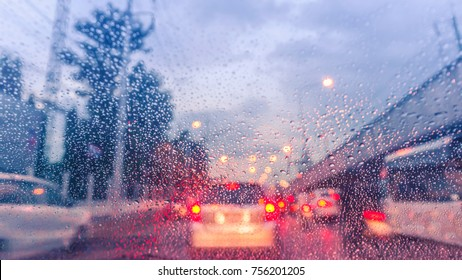 driving car on the road in trafic jam with raindrop over the wind shield, rainy season