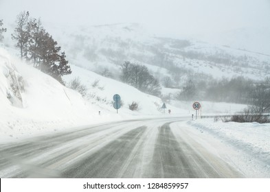 Driving a car on the white and snowy road with a strong wind. Winter weather scene and blizzard. Winter storm. Cars on dangerous frozen and icy road on a mountain pass.  Driving on a snow storm
