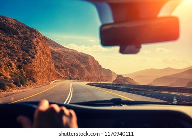 Driving a car on winding mountain road in sunny day. The way from Masada to Arad. View at beautiful mountain landscape from windscreen. Israel