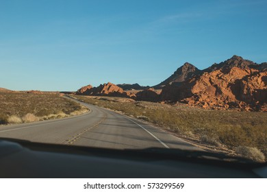 Driving in a car through red rocks in the desert.