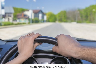 Driving car together. Male and female hands keeping steering wheel car highway background blue sky green forest