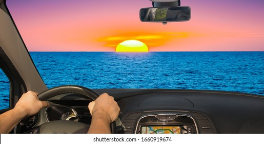 Driving a car towards a beautiful sunset by the mediterranean sea, Italy