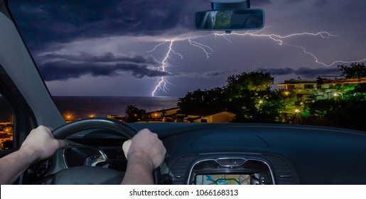 Driving a car towards a spectacular lightning storm over the sea