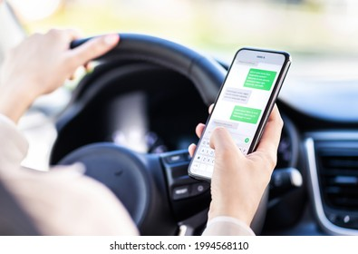 Driving car and using phone. Distracted driver texting with mobile cellphone. Irresponsible woman checking sms message with smartphone in traffic. Auto accident concept. Holding smart device in hand.