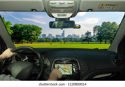 Driving a car while using the touch screen of a GPS navigation system in Central Park with a beautiful contrast between skyscrapers and buildings, Manhattan, New York City, USA