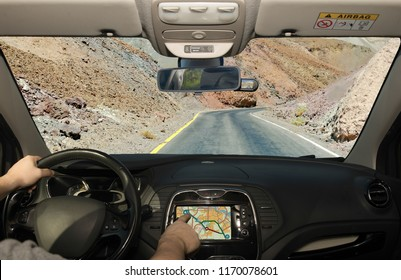 Driving a car while using the touch screen of a GPS navigation system towards a desert road, Death Valley, USA