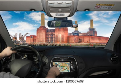 Driving a car while using the touch screen of a GPS navigation system towards Battersea Power Station, London, UK