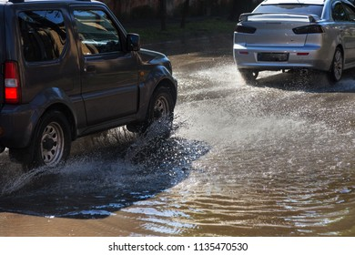 Driving cars on a flooded road during floods caused by rain storms. Cars float on water, flooding streets. Splash on the machine. Flooded city road with a big puddle