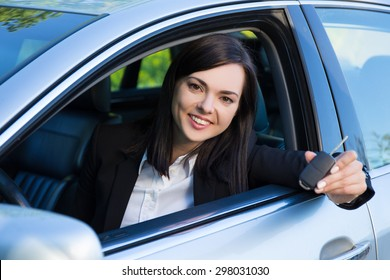 driving concept -happy smiling young woman with car key