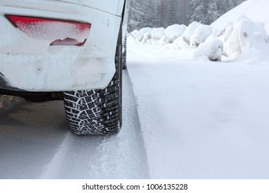Driving in deep snow. Studded winter tires and white car.