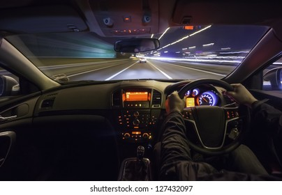 Driving fast after a car on motorway at night.