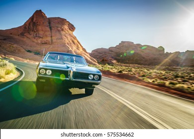 driving fast through desert in vintage hot rod car with lens flare and motion blur