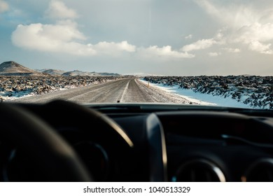 Driving in icelandic winter. Blowing snow across the road. Difficult driving conditions in winter season in Iceland. Sunny but windy day, typical Icelandic route troubles. Icelandic safety driving.