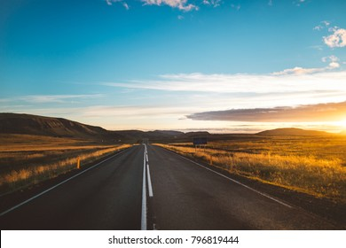 Driving Iceland's ring road self-drive tour.Number 1 road on Iceland, scenic panoramas near the highway.Tourist attraction and campers tour route.Beautiful golden sunset illuminates asphalt road.