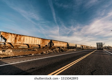 Driving in the middle of nowhere passing a train somewhere along the way on the west coast in California or Oregon, USA.