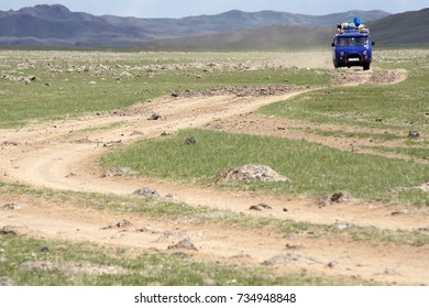 Driving the 'Mongolian Highway' near Naiman Nuur National Park in Mongolia. Blue Soviet-style truck leaving a dust trail on a typical Mongolian dirt road.
