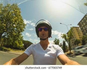 Driving a motorbike on summer. POV selfie. Young adult man driving a motorbike in the city on a sunny summer morning