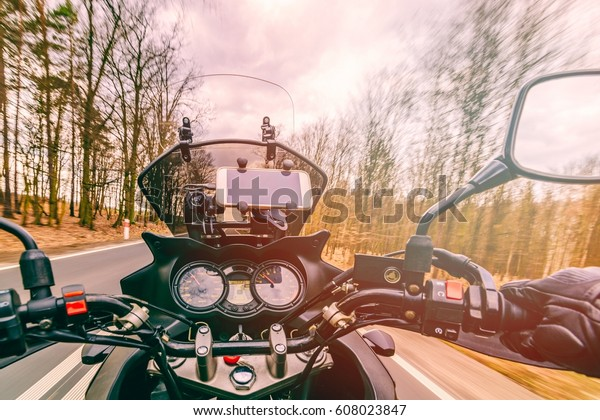 Driving a motorcycle at spring at the asphalt road through forest. First person view