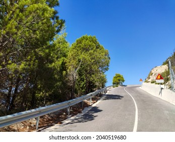 Driving mountain serpentine steep road with warning signs from Gialos pebble beach with clear blue sky, Lefkada island, Greece. Sunny summer scenic day trip